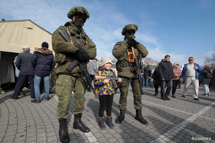 FILE - A child poses for a picture with Russian servicemen during a military equipment and hardware show, on Defender of the Fatherland Day, in Sevastopol, Crimea, Feb. 23, 2020.