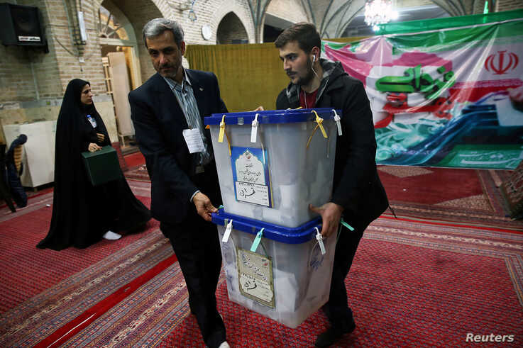 Poll workers carry ballot boxes after voting in parliamentary elections ended, in Tehran, Iran, Feb. 22, 2020.