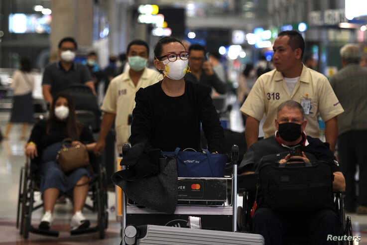 FILE - Passengers are seen wearing protective masks as they arrive at Suvarnabhumi Airport in Bangkok, Thailand, Feb. 20, 2020.