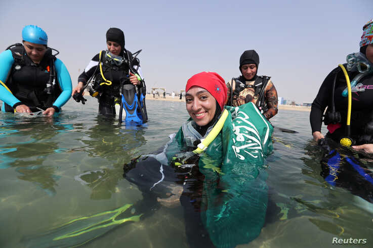 FILE - A female Saudi diver, wearing a Saudi national flag over her shoulders, smiles as she prepares to dive at a dive site in Dhahran, Saudi Arabia, Sept. 15, 2018.