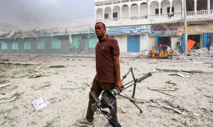 FILE - A Somali journalist holds his camera after he was injured in an explosion in front of Dayah hotel in Somalia's capital Mogadishu, Jan. 25, 2017.
