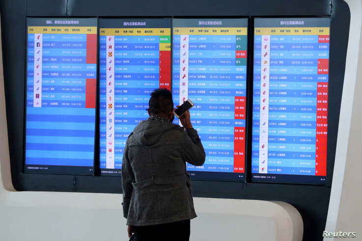 FILE - A man stands in front of a screen showing that multiple departure flights have been cancelled following the outbreak of the coronavirus, at an airport in Wuhan, Hubei province, China, Jan. 23, 2020. (cnsphoto via Reuters)