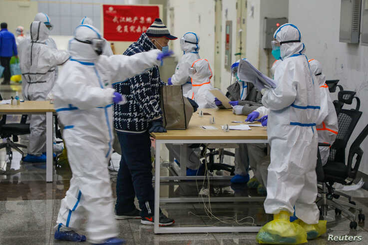 Medical workers in protective suits receive a patient at the Wuhan International Conference and Exhibition Center, which has been converted into a makeshift hospital to receive patients with mild symptoms of the coronavirus, in Wuhan, China Feb. 5, 2020.