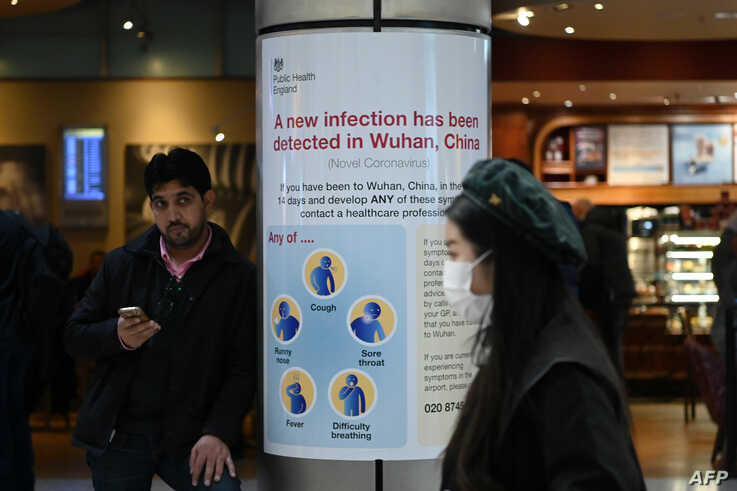 A woman wearing a face mask passes a Public Health England sign, warning arriving passengers that a virus, Coronavirus, has…