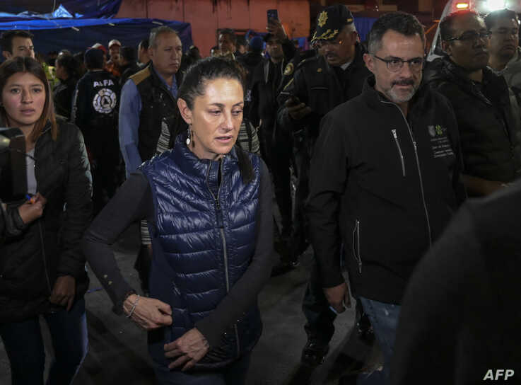 Mexico City's Mayor Claudia Sheinbaum (C) leaves Tacubaya metro station, where two trains collided leaving one dead and 41…