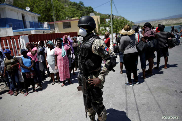 A Haitian National Police (PNH) officer looks on as Haitians stand behind him in the on the border of Malpasse, Haiti, March 17…