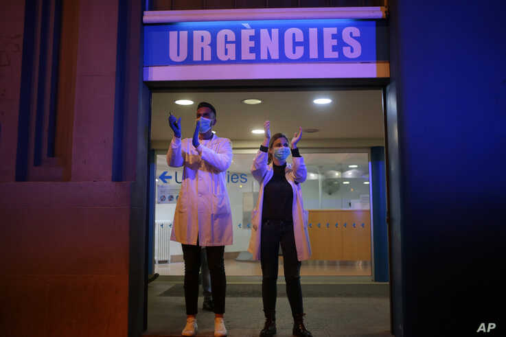 Health workers react as people applaud them from their houses, Barcelona, Spain, March 16, 2020.