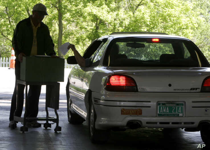 FILE - A voter casts a ballot from an auto in a special election on June 6, 2006 in Williston, Vt.