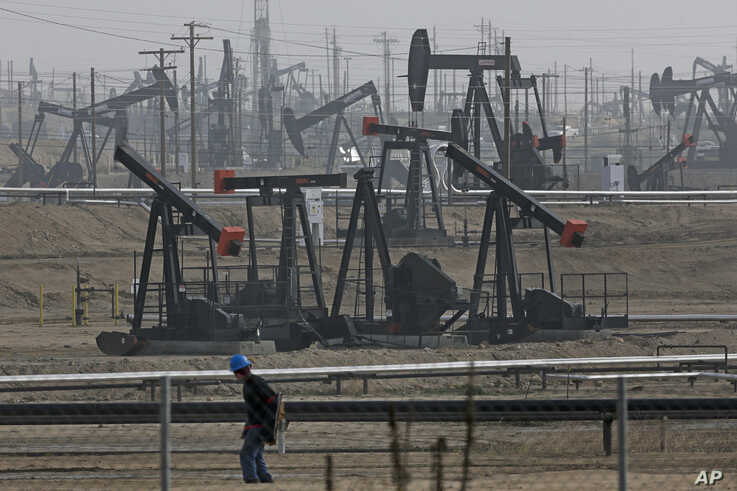 FILE - In this Jan. 16, 2015, file photo, a person walks past pump jacks operating at the Kern River Oil Field in Bakersfield,…