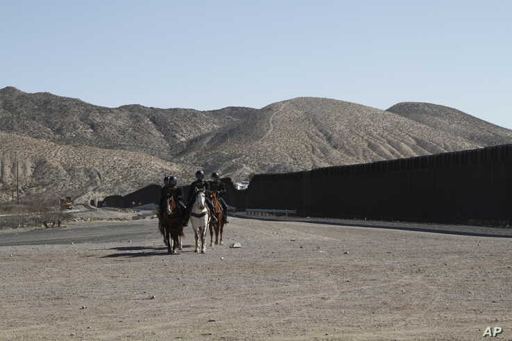 Border Patrol agents on horseback ride along a US-Mexico border fence on Jan. 31, 2020, in nearby town of Sunland Park, New Mexico.