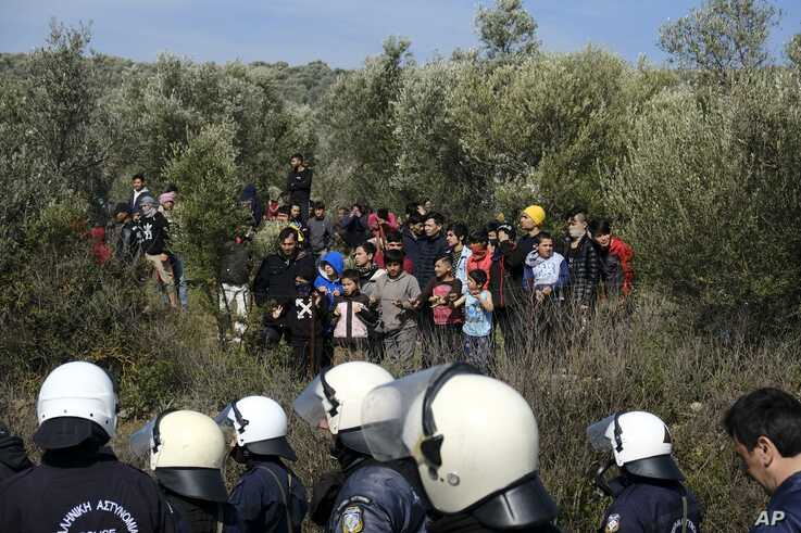 Police block a road as migrants look on during clashes outside the Moria refugee camp on the northeastern Aegean island of…