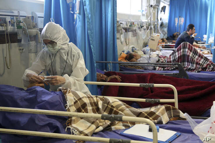 A medic treats a patient infected with the new coronavirus, at a hospital in Tehran, March 8, 2020.