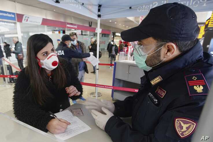 A traveler wears a mask as she fills out a form at a check point set up by border police inside Rome's Termini train station.