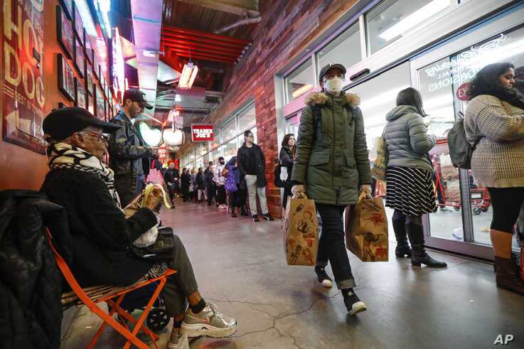 Shoppers wait in a line stretching outside of a Trader Joe's supermarket, March 12, 2020, in the Brooklyn borough of New York.