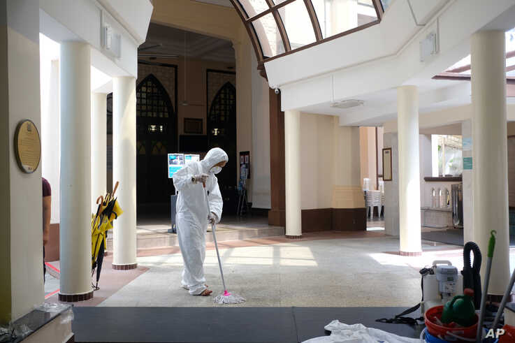 A man wearing a hazmat suit and mask mops the floor inside the Hajjah Fatimah mosque in Singapore on Friday, March 13, 2020…