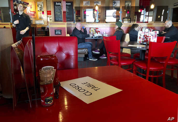 A Red Robin reastaurant in Tigard, Ore., has closed some tables in order to maintain 'social distancing' between diners per CDC…