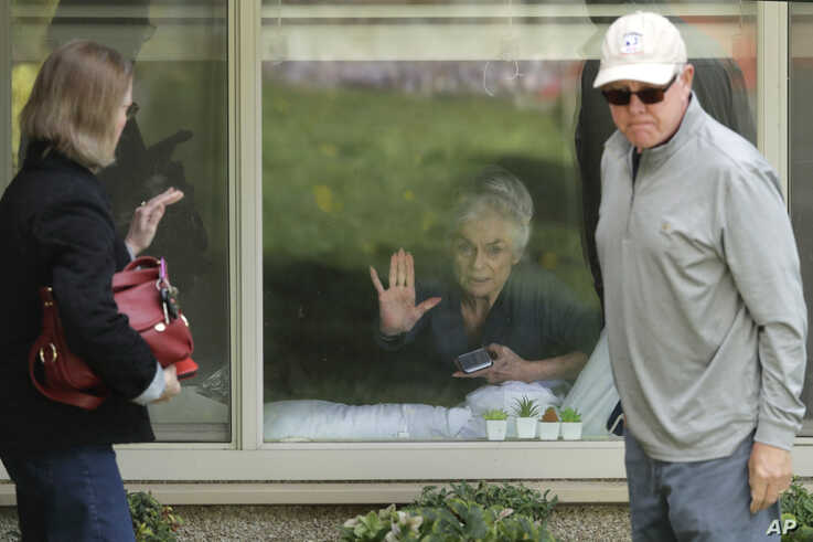 Judie Shape, center, who has tested positive for the coronavirus, but isn't showing symptoms, presses her hand against her window after a visit through the window and on the phone with her relatives, March 17, 2020, in Kirkland near Seattle.