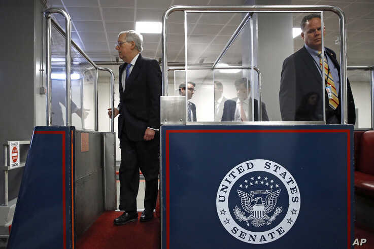 Senate Majority Leader Mitch McConnell of Ky., left, boards a subway car on Capitol Hill in Washington, Wednesday, March 18, 2020, before a vote on a coronavirus response bill.