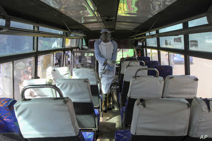 A man sprays disinfectant to sanitize a public bus against the spread of the new coronavirus, in downtown Nairobi, Kenya…