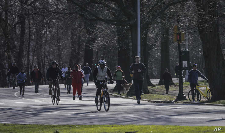 People gather in Brooklyn's Prospect Park as state and city officials urge residents to maintain social distancing to control the growing COVID-19 outbreak, Sunday March 22, 2020, in New York.