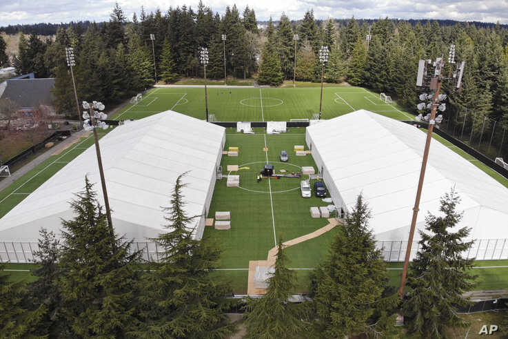 Two massive temporary buildings meant for use as a field hospital for coronavirus patients stand together on a soccer field in the Seattle suburb of Shoreline, Washington, March 24, 2020.