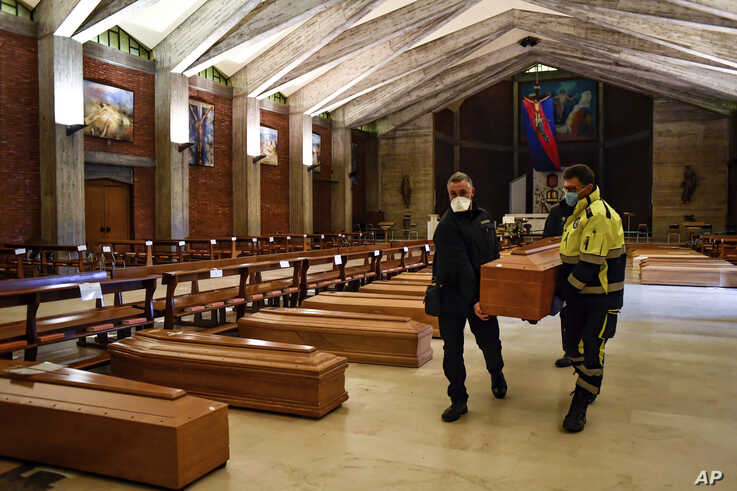 A coffin is carried to be aligned with others on the floor in the San Giuseppe church in Seriate, one of the areas worst hit