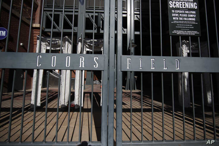 The bars from the closed gate cast long shadows into Coors Field, the home of Major League Baseball's Colorado Rockies, as a…
