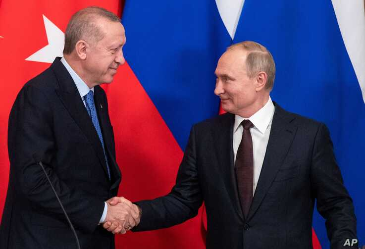 Russian President Vladimir Putin and Turkish President Tayyip Erdogan shake hands during a news conference following their…