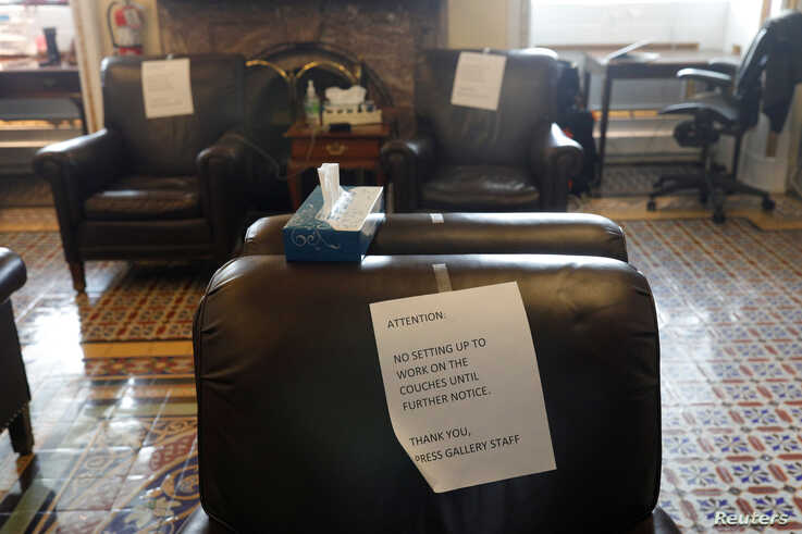 Signs calling for social distancing are posted on chairs used by journalists inside the U.S. Capitol, as Mayor Muriel Bowser…