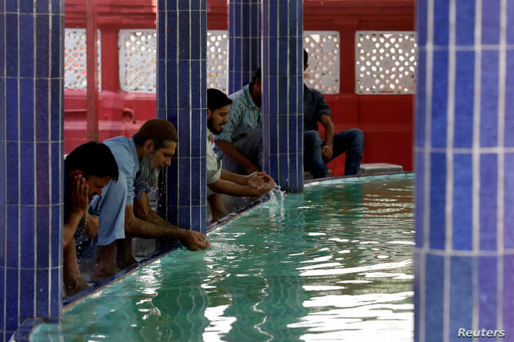 Muslims perform ablution as they gather to attend Friday prayer amid an outbreak of the coronavirus disease (COVID-19), at a…