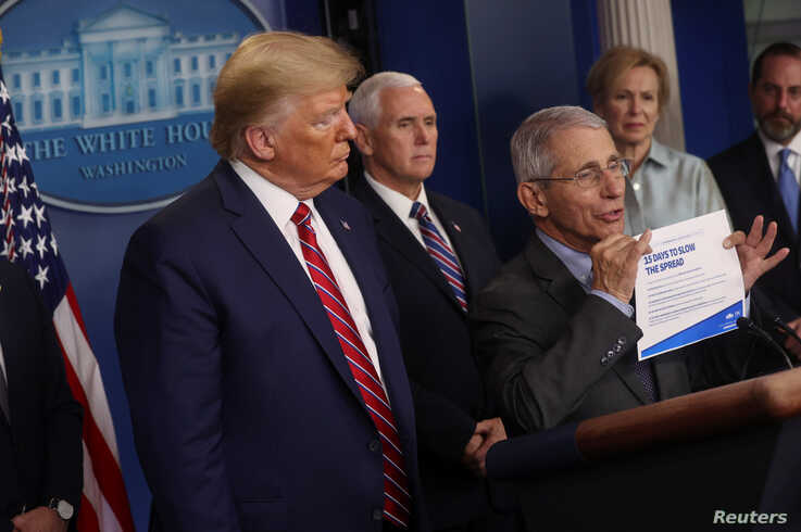 U.S. President Donald Trump listens as National Institute of Allergy and Infectious Diseases Director Anthony Fauci addresses…