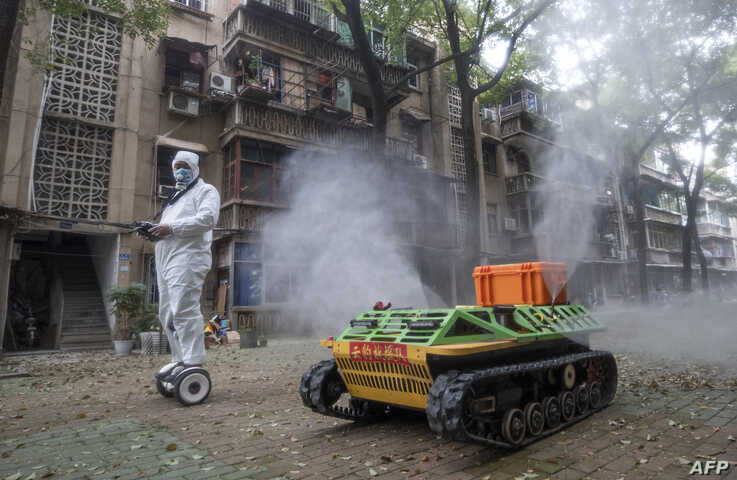 A volunteer operates a remote controlled robot to disinfect a residential area amid the COVID-19 outbreak in Wuhan in China's central Hubei province.