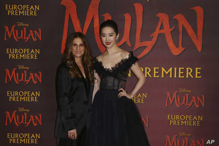 Actress Yifei Liu, right, and Director Niki Caro, left, pose for photographers upon arrival at the European Premiere of 'Mulan' at a central London cinema, March 12, 2020.