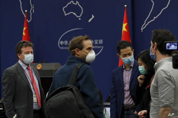 The New York Times Beijing based correspondent Steven Lee Myers, left, chats with other foreign journalists after a daily briefing  at the Ministry of Foreign Affairs office in Beijing, March 18, 2020.