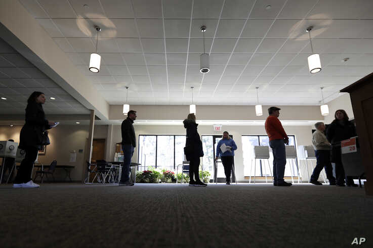 Evanston residents line up to vote at a polling station at Trinity Lutheran Church, in Evanston, Illinois, March 17, 2020.