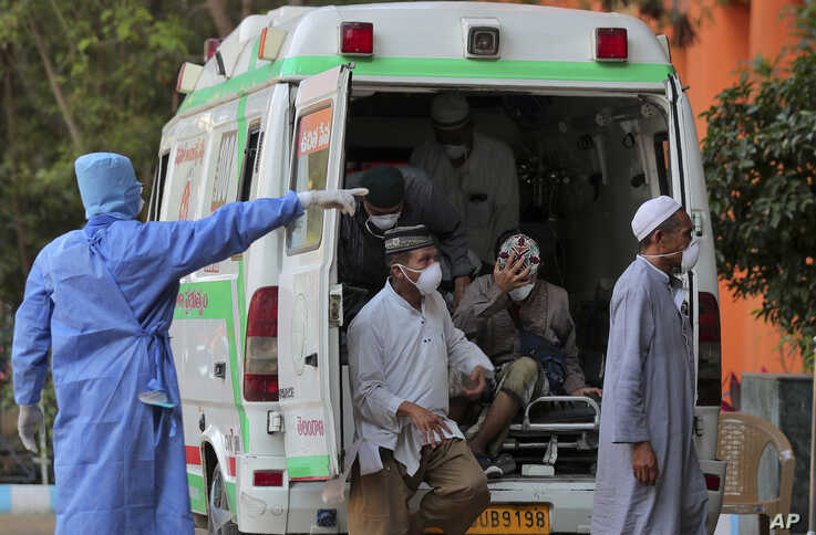 Indonesian tourists with Covid-19 symptoms get off from an ambulance at the Government Gandhi Hospital in Hyderabad, India, March 16, 2020.