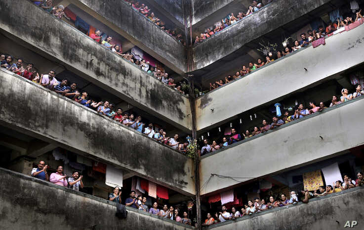 People clap from balconies in show of appreciation to health care workers at a Chawl in Mumbai, India, March 22, 2020.