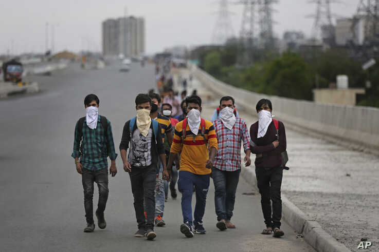 A group of Indian daily wage laborers walk along an expressway hoping to reach their homes, hundreds of kilometers away, as the city comes under lockdown in Ghaziabad, on the outskirts of New Delhi, India, March 26, 2020.