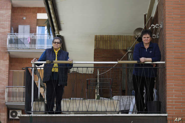 A caregiver (R) keeps her distance from an elderly woman whom she looks after, on the balcony of the woman's home in Rome, March 11, 2020.