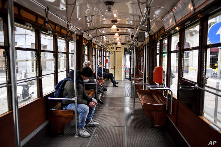 Passengers sit at distance from each others on a tram in Milan, Italy, March 12, 2020.