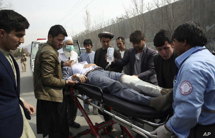 An injured man is moved toward an ambulance, after an attack in Kabul, Afghanistan, March 6, 2020.