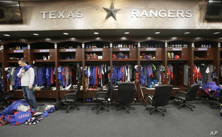 FILE - Texas Rangers pitcher Sam Dyson packs a bag in the locker room at the baseball park in Arlington, Texas, Oct. 11, 2016. Major U.S. sports leagues are closing access to locker rooms and clubhouses to all non-essential personnel.