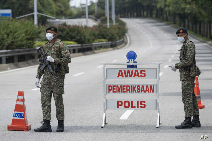 Soldiers in face masks maintain a checkpoint in Putrajaya, Malaysia, March 22, 2020.