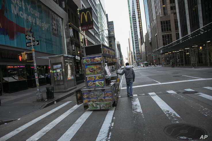 A food truck vendor pushes his cart down an empty street near Times Square in New York, March 15, 2020.