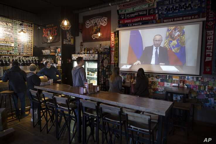 A few visitors and staff of a pub watch the broadcast of Russian President Vladimir Putin's address to the nation, in Moscow, Russia, March 25, 2020.