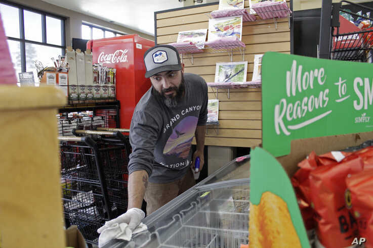 In this photo taken March 20, 2020, Mike Johnston, a clerk at the Maupin Market in Maupin, Oregon, wipes down the ice cream case to protect customers from the coronavirus.