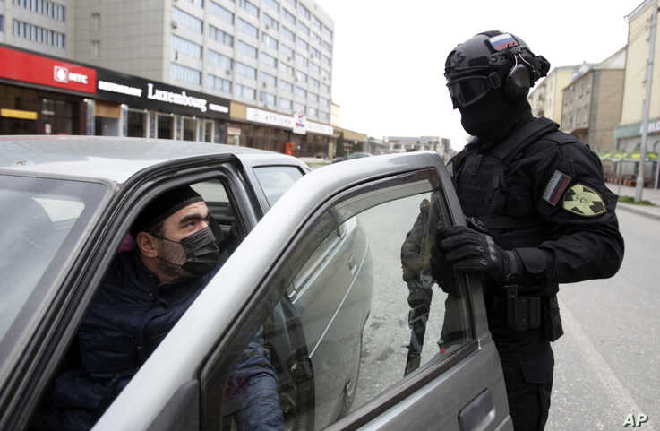 A police officer wearing a protective mask and glasses stops a car driver to check his documents in Grozny, Russia, March 30, 2020.