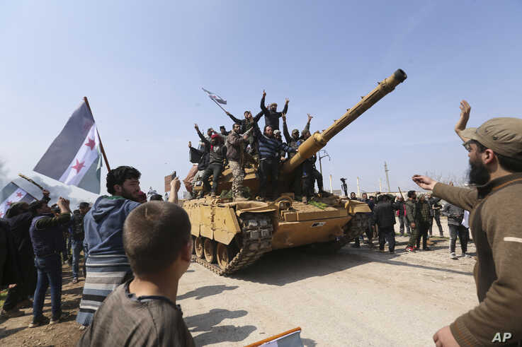 Syrians climb on a Turkish tank in Neyrab, March 15, 2020, as they protest agreement on joint Turkish and Russian patrols in northwest Syria.