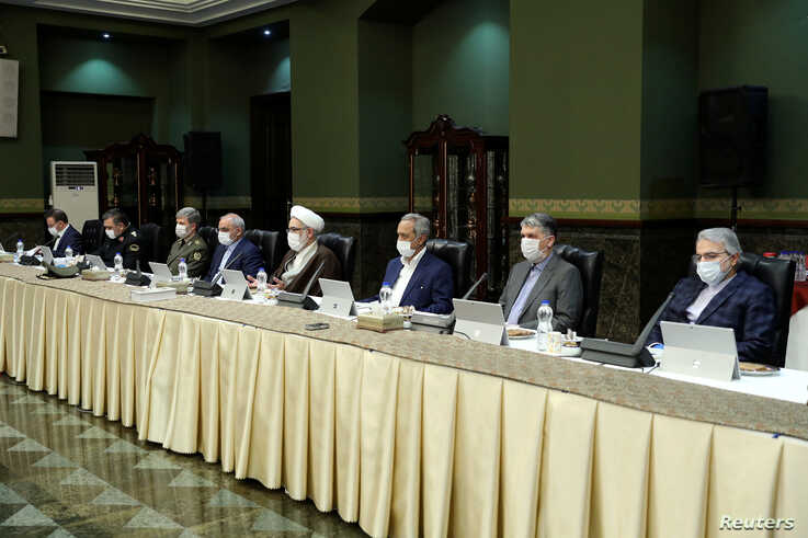 Senior officials wear face masks as they attend a meeting of the Iranian government task force on the coronavirus, in Tehran, Iran, March 21, 2020.