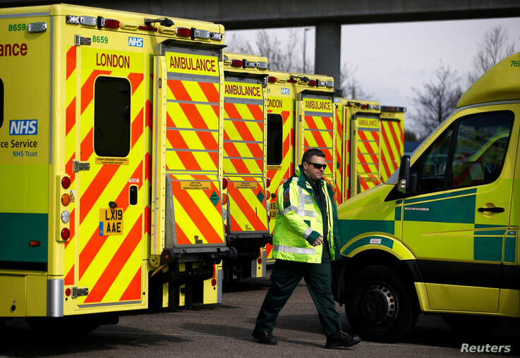 A paramedic walks amid ambulances outside London's Excel Centre, while it is being prepared to become a hospital for the treatment of coronavirus patients, in London, Britain, March 28, 2020.